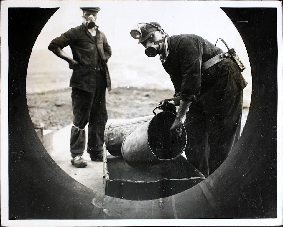 Men wearing respirators loading a four-foot wide tube with coal dust on a hilltop at Harpur Hill, Derbyshire, before detonating it in a controlled explosion for an experiment. A handful of men at the site are fighting continually against the causes of coal mine disasters. Coal dust, under certain conditions, is as dangerous as high explosive and these men are experimenting every day to find an effective method of combatting the menace. A four foot wide tube to represent a mine shaft is filled with coal dust and purposely exploded, then the burnt out dust is analysed. More deaths are caused by the gas (firedamp or methane) than the actual explosion.  (Photo by Fox Photos/Hulton Archive/Getty Images)