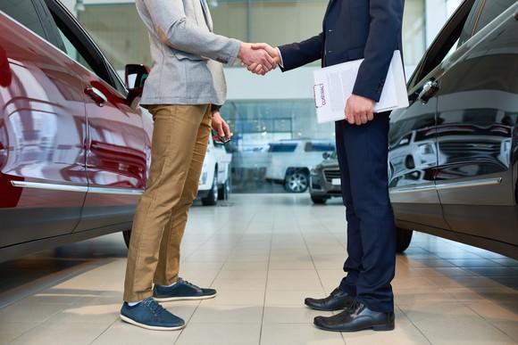 A male customer shakes hands with a car salesman.