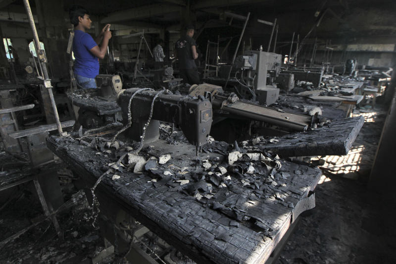 A man takes photographs inside a garment-factory where a fire killed more than 110 people Saturday on the outskirts of Dhaka, Bangladesh, Monday, Nov. 26, 2012. Bangladeshi workers protested blocks from the gutted fire Monday, demanding justice for the victims and improved safety. Some 200 factories were closed for the day after the protest erupted in Savar, a suburb of Dhaka, the capital. (AP Photo)