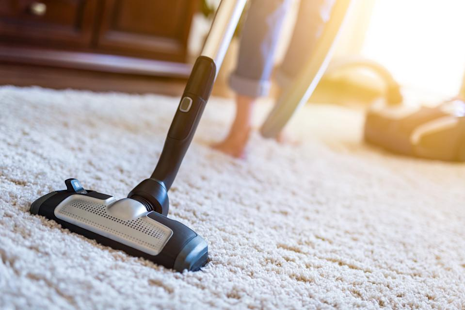 Young woman using a vacuum cleaner while cleaning carpet in the house.