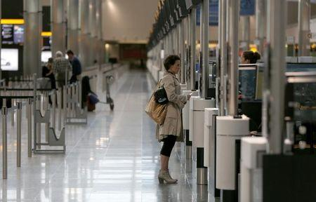 A woman checks-in in Terminal 2 at Heathrow Airport in London