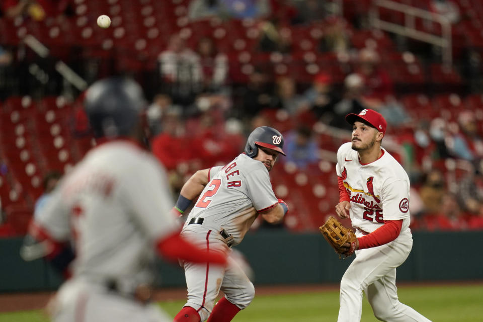 St. Louis Cardinals third baseman Nolan Arenado, right, runs to catch a bunt popped up by Washington Nationals' Josh Harrison, left, for an out as Nationals' Kyle Schwarber, center, heads back to third during the sixth inning of a baseball game Monday, April 12, 2021, in St. Louis. (AP Photo/Jeff Roberson)