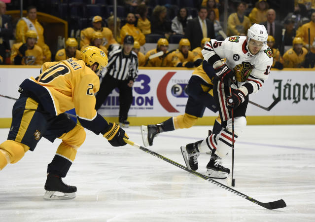 Chicago Blackhawks center Artem Anisimov (15), of Russia, moves the puck away from Nashville Predators right wing Miikka Salomaki (20), of Finland, during the second period of an NHL hockey game Saturday, Dec. 1, 2018, in Nashville, Tenn. (AP Photo/Mark Zaleski)