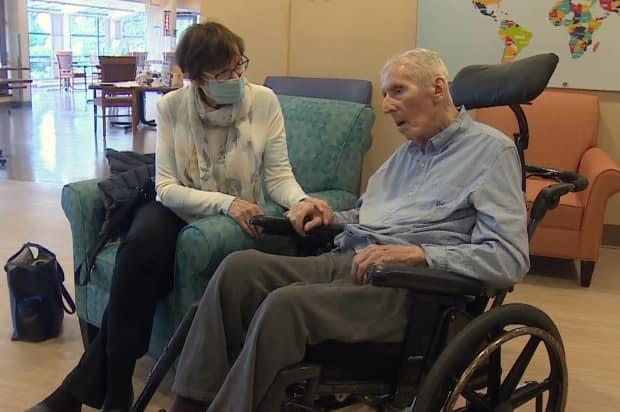 Lucille and Harry Minuk hold hands for the first time since the COVID-19 pandemic began. Harry is a resident at Three Links Care Centre in Vancouver.
