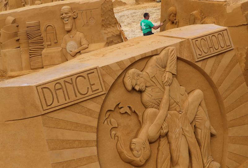 "A sand carver works on a sculpture during the Sand Sculpture Festival ""Dreams"" in Ostend, Belgium June 18, 2019. (Photo: Yves Herman/Reuters)"