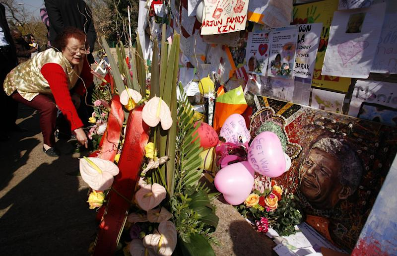 Unidentified welwisher lays flowers outside the Mediclinic Heart Hospital where former South African President Nelson Mandela, is being treated in Pretoria, South Africa Sunday, June 30, 2013. (AP Photo/Themba Hadebe)