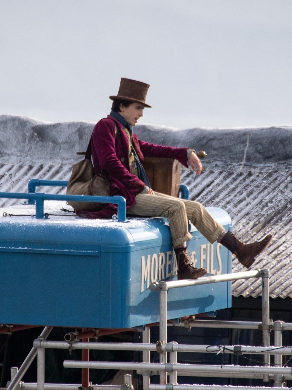 <p>Timothée's beige striped trousers are rolled to the calves to show off some worn-in lace-up boots. Also, in this take, he's subbed in a simple navy scarf in lieu of the previous patterned one.</p>