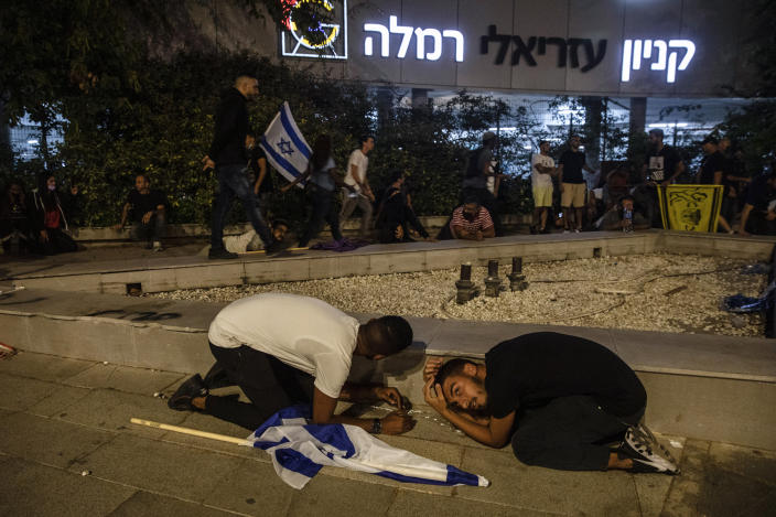 Jewish nationalist demonstrators take cover during a barrage of rockets fired from the Gaza Strip toward central Israel, in the Israeli town of Ramla, Tuesday, May 11, 2021. The protesters had gathered in an attempted show of strength in a predominantly Arab neighborhood. (AP Photo/Heidi Levine)