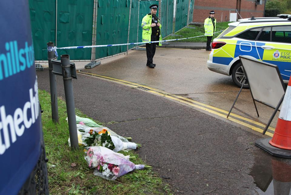 THURROCK, ENGLAND - OCTOBER 24: Flowers lay next to a police line cordon at the scene where 39 bodies discovered in the back of a lorry on October 24, 2019 in Thurrock, England. The lorry was discovered early Wednesday morning in Waterglade Industrial Park on Eastern Avenue in the town of Grays. (Photo by Zhang Ping/China News Service/VCG via Getty Images)