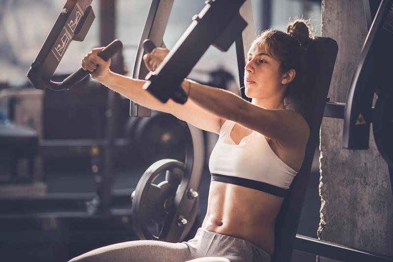 Young athletic woman doing strength exercises on a machine in a health club.