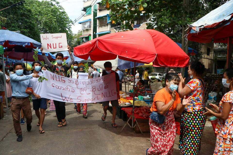 """Anti-coup protesters hold signs that read """"We Support NUG"""" that stands for 'national unity government' as they march on a street where vendors sell fresh products Saturday, April 17, 2021 in Yangon, Myanmar. Opponents of Myanmar's ruling junta have declared they have formed an interim national unity government with members of Aung San Suu Kyi's ousted cabinet and major ethnic minority groups.. (AP Photo)"""