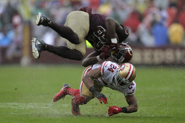 Washington Redskins tight end Jeremy Sprinkle, top, flips over San Francisco 49ers defensive back K'Waun Williams as he rushes the ball in the second half of an NFL football game, Sunday, Oct. 20, 2019, in Landover, Md. (AP Photo/Julio Cortez)