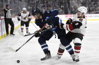 Arizona Coyotes' Clayton Keller (9) checks Winnipeg Jets' Blake Wheeler (26) during the second period of an NHL hockey game Tuesday, Oct. 15, 2019, in Winnipeg, Manitoba. (Fred Greenslade/The Canadian Press via AP)