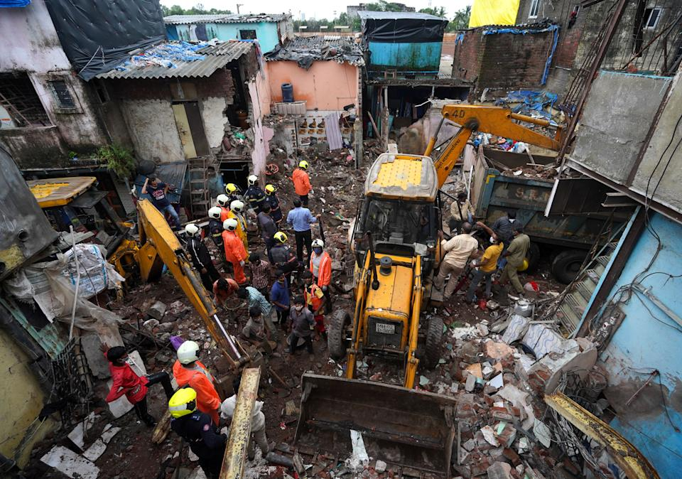 Rescue workers remove debris to search for survivors after a residential building collapsed on top of another building in Mumbai, India, June 10, 2021. REUTERS/Hemanshi Kamani