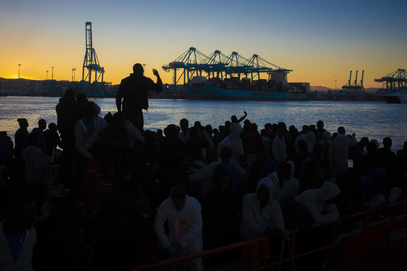In this photo taken late Wednesday, July 25, 2018, migrants are silhouetted as they prepare to spend the night onboard a Spanish Maritime Rescue Service boat docked at the port of Algeciras, southern Spain, after being rescued in the Strait of Gibraltar. Around 800 migrants stormed border fences separating Spain's North African enclave of Ceuta from Morocco to get into Europe, police said Thursday. (AP Photo/Marcos Moreno)