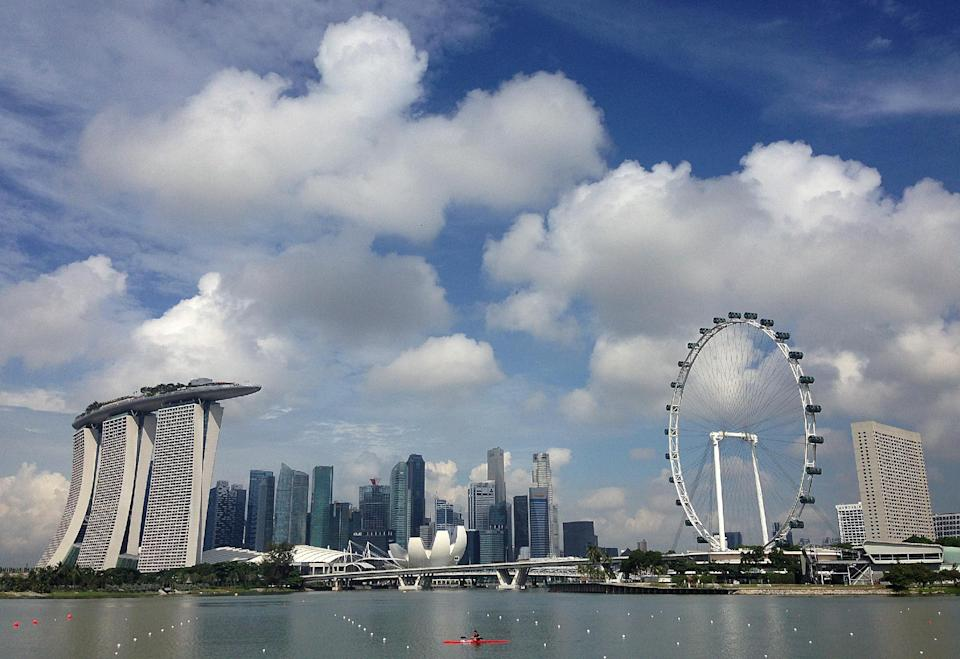 A man paddling his kayak is dwarfed against the skyline of the Marina Bay, which is home to popular hotels, and tourist attractions such as the Singapore Flyer, seen at right, Monday, April 27, 2015, in Singapore. The city-state's government announced earlier in the year, new plans for its global marketing campaign to tap on the country's year-long 50th birthday celebration, as part of its continued effort to boost tourism numbers in 2015, after the country went through a challenging season in 2014. (AP Photo/Wong Maye-E)
