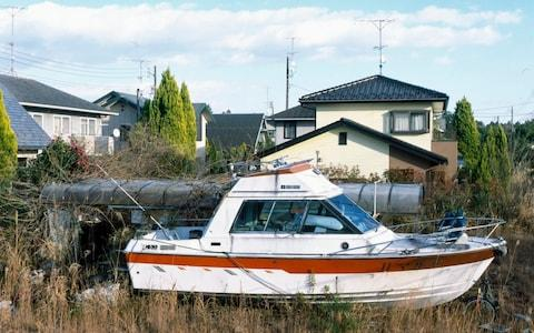 A yacht lies in the backyard of an abandoned home inside the contamination zone - Credit: Simon Townsley