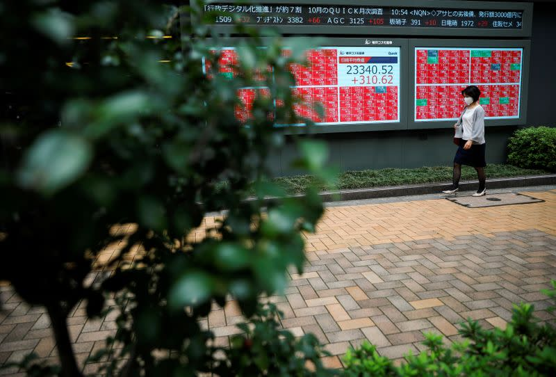 FILE PHOTO: A passersby wearing a protective face mask walks in front of a stock quotation board, amid the coronavirus disease (COVID-19) outbreak, in Tokyo