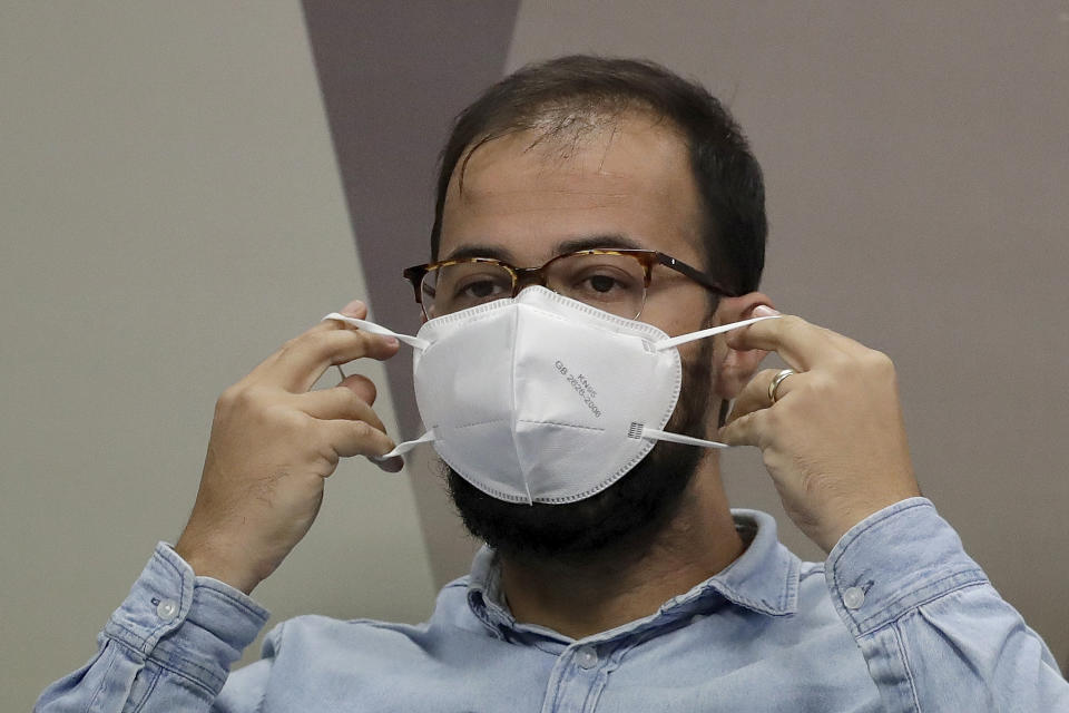 Luis Ricardo Fernandes Miranda, head of Import of the Department of Logistics of the Ministry of Health, adjusts his face protective mask, during his testimony before the Senate for an investigation into the government's management of the COVID-19 pandemic, in Brasilia, Brazil, Friday, June 25, 2021. (AP Photo/Eraldo Peres)