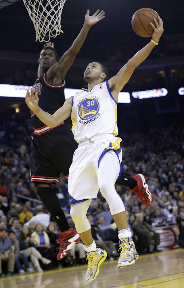 Golden State Warriors' Stephen Curry (30) scores past Chicago Bulls' Jimmy Butler during the second half of an NBA basketball game on Thursday, Feb. 6, 2014, in Oakland, Calif. Golden State won 102-87. (AP Photo/Marcio Jose Sanchez)