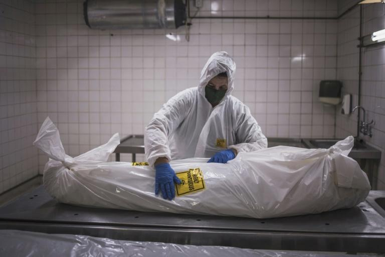 A morgue attendant at the Pretoria branch of the South African funeral and burial services company Avbob applies a biohazard warning on the body of COVID-19 victim