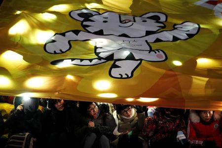 Women watch the Olympic torch relay under a giant banner depicting the 2018 PyeongChang Winter Olympics mascot Soohorang, in Seoul, South Korea