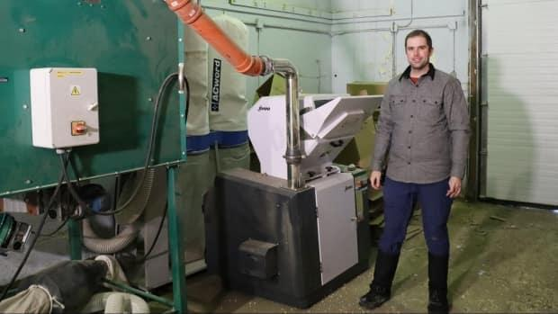 Patrick Gall of the Aurora Research Institute in Inuvik, N.W.T., is shown alongside a machine that turns waste cardboard into pellets that can be used to fuel for boilers. (Patrick Gall - image credit)