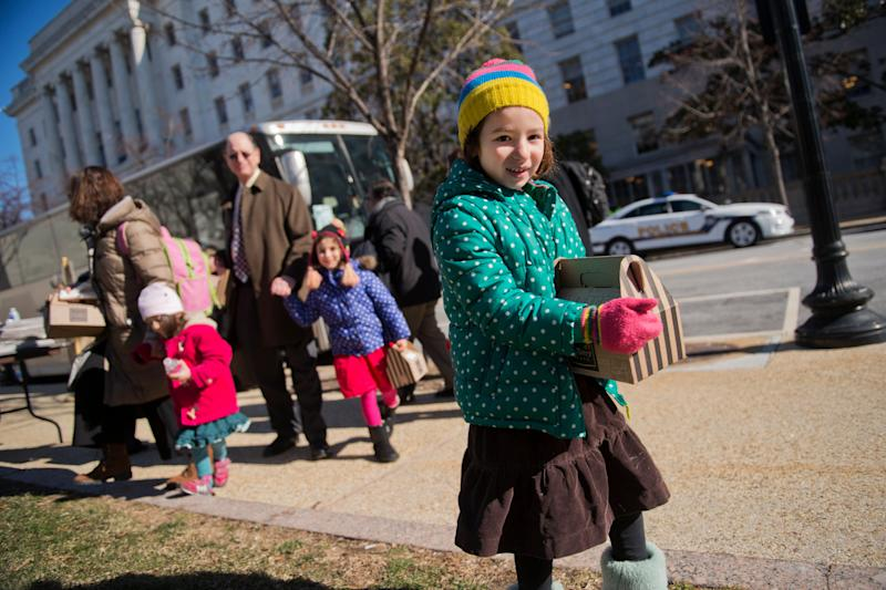 Naomi Sherman, 4, right, along with her father, Rep. Brad Sherman (D-Calif.); mother, Lisa; and sisters, Lucy, 2, and Molly, 5, prepares to board a bus that will take House Democrats and their families to a retreat in Philadelphia on Jan. 28, 2015.