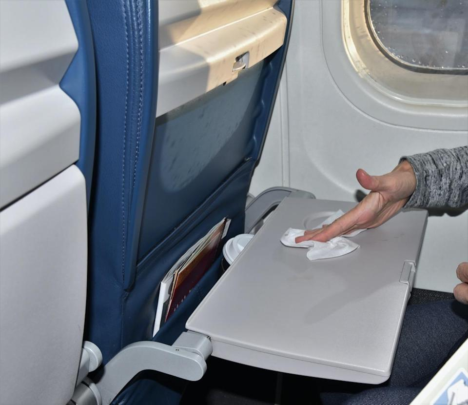 A woman sitting by a window seat is wiping down a germ laden dirty airplane tray with an antibacterial wipe