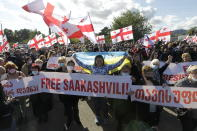 Georgian opposition supporters of former president Mikheil Saakashvili hold Georgian and Ukrainian national flags during a rally in his support in front of the prison where former president is being held, in Rustavi, about 20 km from the capital Tbilisi, Georgia, Monday, Oct. 4, 2021. Saakashvili was detained in Tbilisi on Saturday, Oct. 1, 2021. Georgia earlier declared Saakashvili wanted as a person convicted in absentia in several criminal cases and treated as a suspect in some others. Georgian authorities have warned repeatedly that he would be detained immediately once over the border. (AP Photo/Shakh Aivazov)