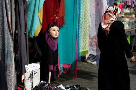 A woman walks past a mannequin wearing an hijab headscarf at a market in the Brussels district of Molenbeek