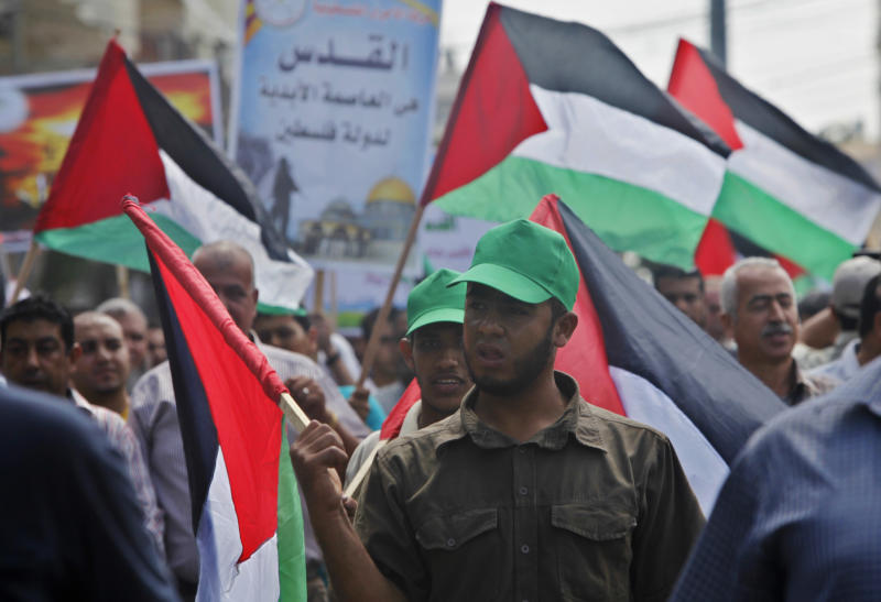 Palestinians wave their national flags during a protest to condemn what protesters claim was a desecration of Al-Aqsa Mosque in Jerusalem by Jewish extremists, in Gaza City, Wednesday, Sept. 4, 2013. Israeli police spokesman Micky Rosenfeld says that clashes in Jerusalem erupted Wednesday when some 300 Palestinian demonstrators tried to block a group of visitors from reaching the sensitive hilltop compound revered by both Jews and Muslims. Israeli police arrested seven Palestinians after clashes between stone-throwing demonstrators and Israeli security forces. (AP Photo/Adel Hana)