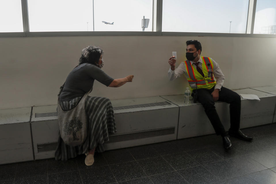 Elissa Montanti, founder and director of the Global Medical Relief Fund, hands her card to an Emirates airline employee while waiting for amputee children from Tanzania to arrive at JFK International Airport, Friday, May 28, 2021, in New York. The pandemic put a hold on international travel, and on the services Montanti has facilitated for the more than 450 kids who have passed through her care. As restrictions have begun lifting across the country, the Staten Island woman is bringing her charity back to life. (AP Photo/Julie Jacobson)