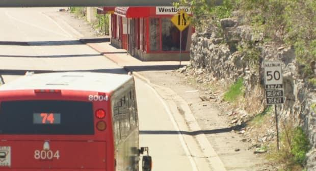 A westbound double-decker pulls into Westboro station on May 13, 2021. The posted speed limit is 50 km/h and there are no visible changes to the placement of the shelter or structure of the platform from 2019.