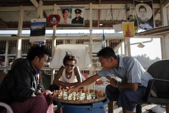 People play chess near pictures of pro-democracy leader Aung San Suu Kyi and her father and country's independence hero General Aung San at a market in capital Naypyitaw, January 24, 2012.