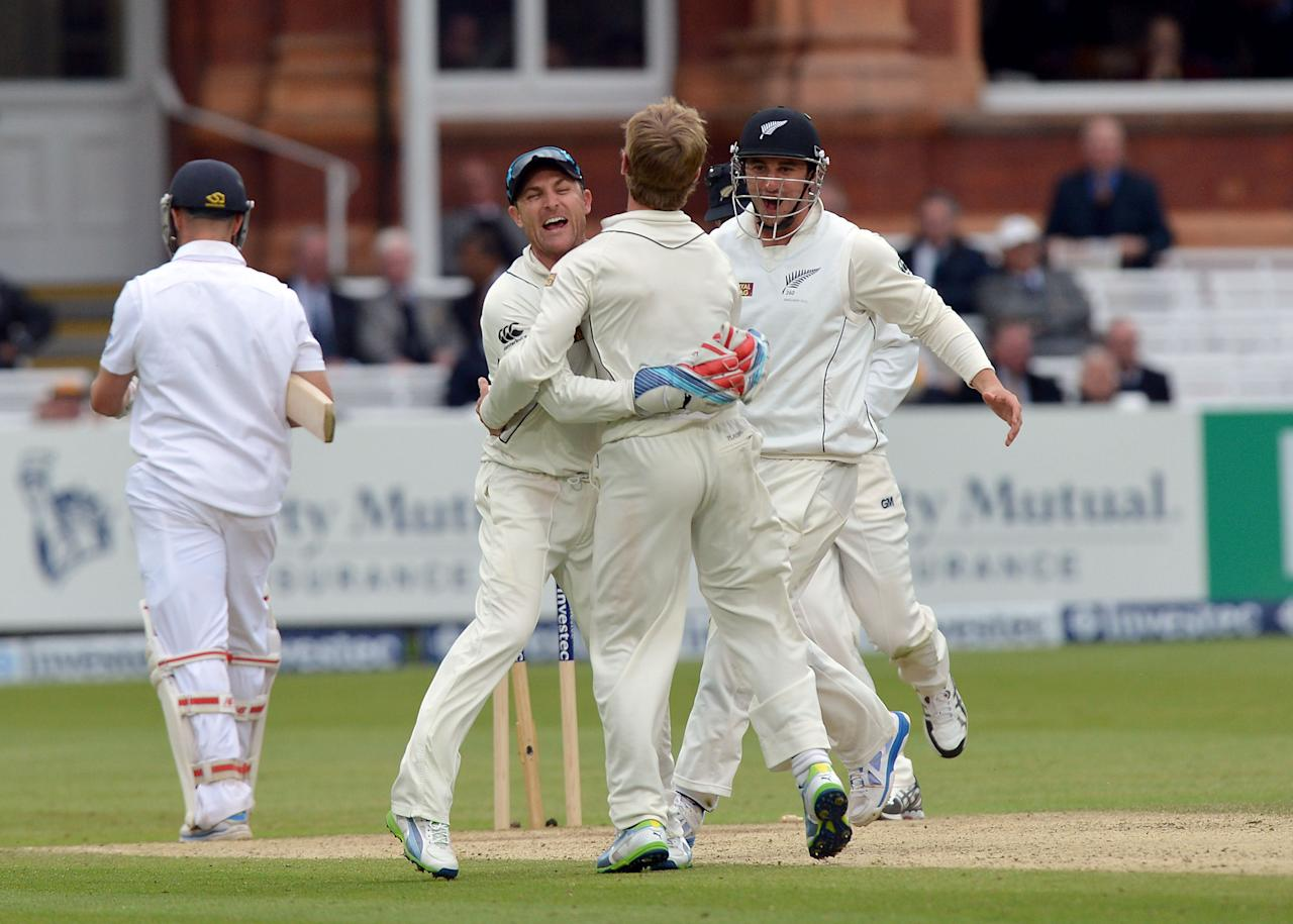 New Zealand's Kane Williamson (centre) is congratulated by Brendon McCullum (second left) and Hamish Rutherford (right) after taking the wicket of England's Jonathan Trott for 56 during the first test at Lord's Cricket Ground, London.