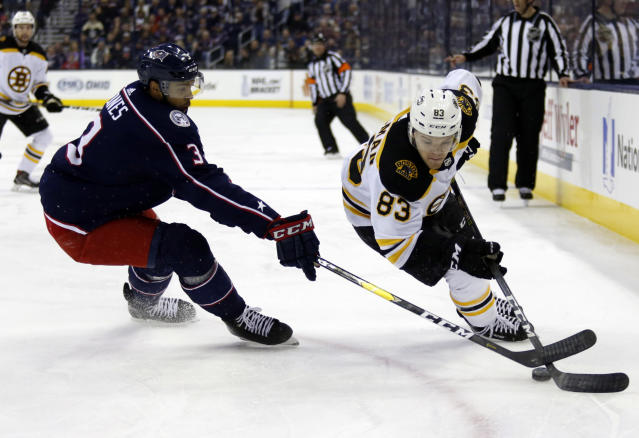 Columbus Blue Jackets defenseman Seth Jones, left, works against Boston Bruins forward Karson Kuhlman during the first period of an NHL hockey game in Columbus, Ohio, Tuesday, April 2, 2019. (AP Photo/Paul Vernon)
