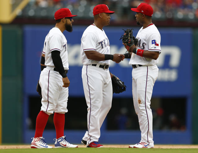 Texas Rangers third baseman Adrian Beltre, center, shakes hands with Elvis Andrus, right, while leaving a baseball game as Rougned Odor, left, watches during the sixth inning against the Seattle Mariners, Sunday, Sept. 23, 2018, in Arlington, Texas. (AP Photo/Jim Cowsert)