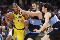 Indiana Pacers' T.J. Warren (1) drives past Cleveland Cavaliers' Kevin Love (0) and Cleveland Cavaliers' Cedi Osman (16) in the second half of an NBA basketball game, Saturday, Feb. 29, 2020, in Cleveland. Indiana won 113-104. (AP Photo/Tony Dejak)