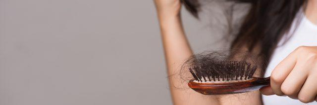 Woman with long brown hair holds a brush out to show hair loss