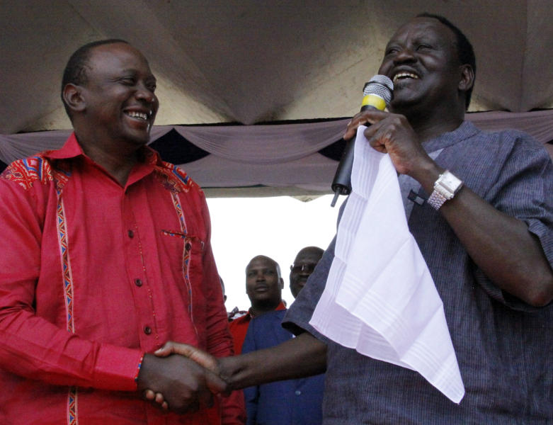 FILE - In this Feb. 24, 2013 file photo, Orange Democratic Movement (ODM) Presidential candidate Raila Odinga, right, shakes hands with The National Alliance (TNA) Presidential candidate Uhuru Kenyatta, left, during an election rally in Uhuru Park in Nairobi, Kenya. The toll of more than 1,000 dead after Kenya's last election makes the presidential vote on Monday, March 4, 2013 the most important in the country's 50-year history, while a slate of new races and a presidential candidate Uhuru Kenyatta who faces charges at the International Criminal Court also make it Kenya's most complicated. (AP Photo/Khalil Senosi, File)