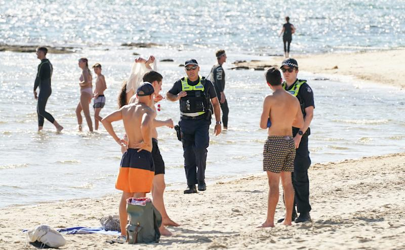 Police officers inform beachgoers that the Brighton Beach is closed as on-the-spot fines for people who breach social distancing rules during coronavirus