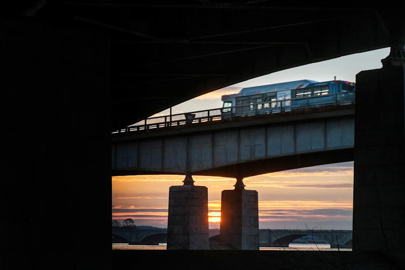 In this photograph made Tuesday, Dec. 31, 2013 a Washington Metro bus rolls across the Roosevelt Bridge over the Potomac River in Washington. Americans are riding on buses, trains and subways in greater numbers according to a report released by the American Public Transportation Association. (AP Photo/J. David Ake)