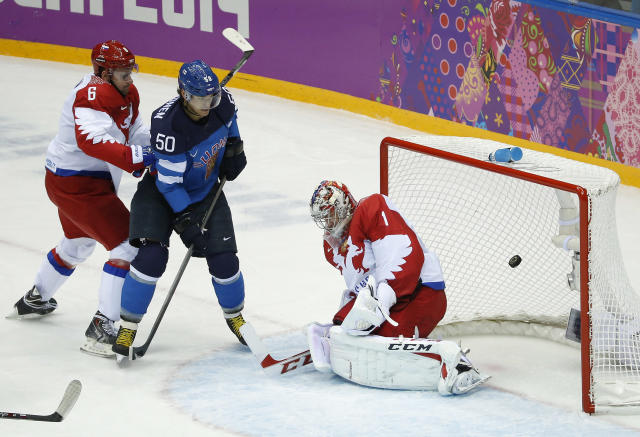 Finland forward Juhamatti Aaltonen (50) scores against Russia defenseman Nikita Nikitin, left, and Russia goaltender Semyon Varlamov in the first period of a men's quarterfinal ice hockey game at the 2014 Winter Olympics, Wednesday, Feb. 19, 2014, in Sochi, Russia. (AP Photo/Mark Humphrey)