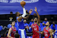 Los Angeles Lakers' LeBron James, second from left, goes up for a shot against Philadelphia 76ers' Furkan Korkmaz, from left, Tobias Harris and Ben Simmons during the first half of an NBA basketball game, Wednesday, Jan. 27, 2021, in Philadelphia. (AP Photo/Matt Slocum)