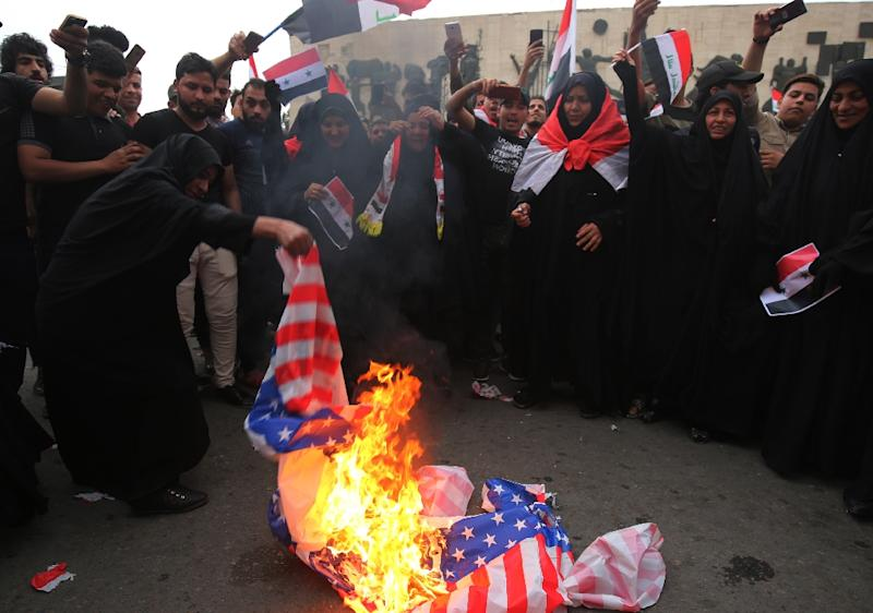 Iraqi protesters in Baghdad burn the US flag as they protest against US strikes in Syria on 15 April, 2018 (AFP Photo/AHMAD AL-RUBAYE)