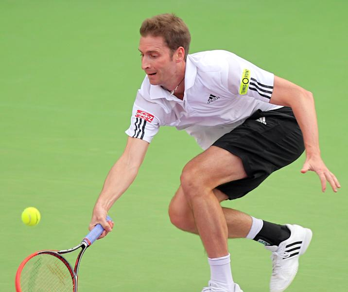 Florian Mayer of Germany returns the ball to Andy Murray of Great Britain during the Qatar ATP Open Tennis tournament in Doha, Qatar, Wednesday, Jan. 1, 2014.(AP Photo/Osama Faisal)