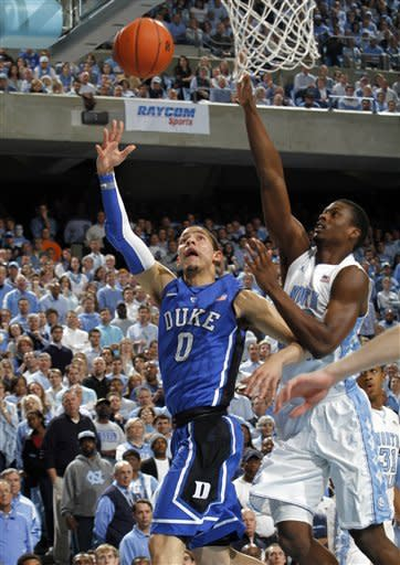 Duke guard Austin Rivers (0) drives to the basket against North Carolina forward Harrison Barnes during the first half of an NCAA college basketball game in Chapel Hill, N.C., Wednesday, Feb. 8, 2012. (AP Photo/Jim R. Bounds)