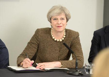 Britain's Prime Minister Theresa May signs a Swansea City deal during a meeting at the Liberty Stadium in Swansea
