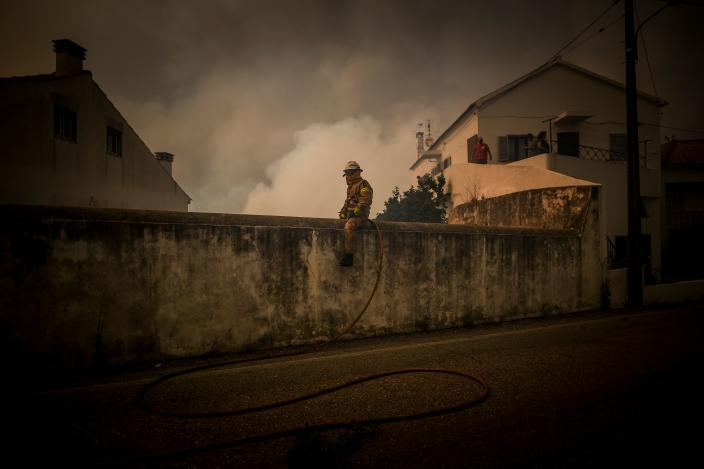 A National Guard Firefighter sits on top of a wall as a wildfire approaches Cardigos village in Macao, central Portugal on July 21, 2019. (Photo: Patricia De Melo Moreira/AFP/Getty Images)